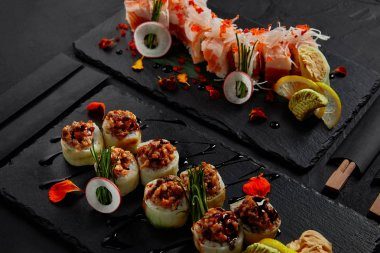 roll in mamenori with shrimp, salmon and avocado in sauce nigiri and roll with creamy eel and kimchi mayonnaise