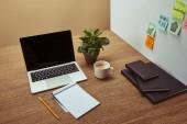 pohled z vysokého úhlu laptop, zápisník a tužka na dřevěnou desku, samolepky na zeď