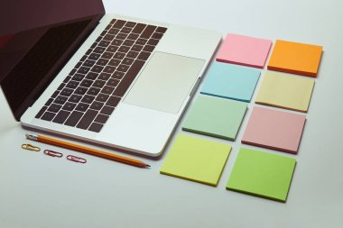 laptop, set of colored paper stickers, pencil and paper clips on white tabletop