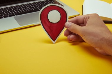 cropped image of man holding paper location sign near laptop