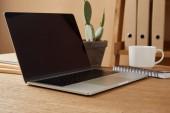 Fényképek laptop-val üres képernyő és csésze kávé asztal