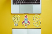 Fotografie elevated view of laptop, paper lightbulb, paper rocket, dollar sign and notebook on yellow surface