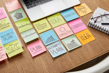 high angle view of paper stickers with business strategy and laptop on tabletop