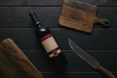 Fotografie top view of wine bottle with blank label, knife and wooden cutting boards
