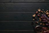 Photo top view of fresh ripe grapes, walnuts, sliced salami and jam on wooden background