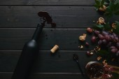 top view of wine bottle, cork and grapes with nuts on wooden surface