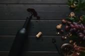 pohled shora láhev vína, korku a hrozny s ořechy na dřevěný povrch