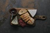 Fotografie pohled shora krájený chléb, lahodné sýry, salámy a jam na dřevěném prkénku