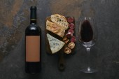 Fotografie top view of bottle and glass of red wine and delicious snacks on cutting board