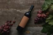 pohled shora láhev vína s prázdný popisek a čerstvých zralých hroznů se zelenými listy na dřevěný stůl