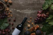 top view of wine bottle with blank label, fruits and delicious jam on wooden table