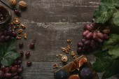 Photo top view of sliced figs on cutting board, fresh ripe grapes, jam and walnuts on wooden table