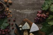 Photo top view of fresh ripe grapes with green leaves, walnuts, delicious  cheese and jam on wooden table