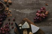 Photo top view of fresh ripe grapes, walnuts, cheese and delicious jam on wooden table
