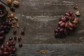 top view of fresh ripe grapes, walnuts and delicious jam on wooden table