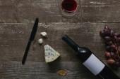 pohled shora na láhev vína s prázdný popisek, skla s červeným vínem, sýry, hrozny a nůž na dřevěný stůl