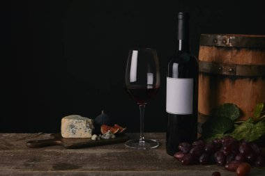 close-up view of glass, bottle and barrel of wine with cheese and grapes on wooden table