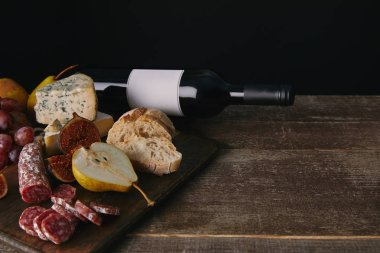 close-up view of bottle of wine with blank label, fruits and delicious snacks on wooden table
