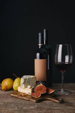 close-up view of bottles and glass of red wine, delicious cheese, figs and pears on wooden table