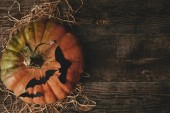 Photo top view of pumpkin and paper bats on wooden table, halloween concept
