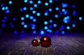 Fotografie red christmas balls on wooden table with blue shiny background