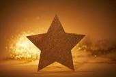 golden glittering star for christmas decoration on tabletop