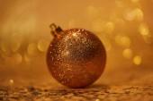 Fotografia lucidando sfera dorata di Natale per la decorazione su tavolo