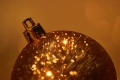 close up of golden glittering christmas ball for decoration isolated on brown