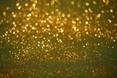golden and green bokeh christmas background with shiny glitter