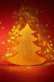 Krásný zlatý třpytivý vánoční strom pro dekoraci na červeném pozadí