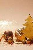 Vánoční koule, třpytivé vánoční strom a zvlněná stuha na desku stolu