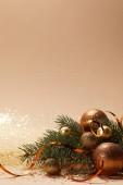 Fényképek glittering golden christmas balls and christmas tree branch on tabletop