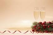 sklenic šampaňského, světlé vánoční koule a borové větve na komentovat stolní