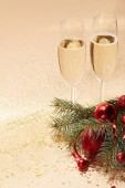 glasses of champagne, red shiny christmas balls and pine branch on glossing golden tabletop