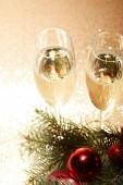 high angle view of glasses of champagne, christmas balls and pine branch on glittering tabletop