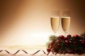 glasses of champagne, christmas balls and pine branch on glittering tabletop