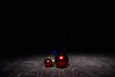 red christmas balls on wooden table with black background