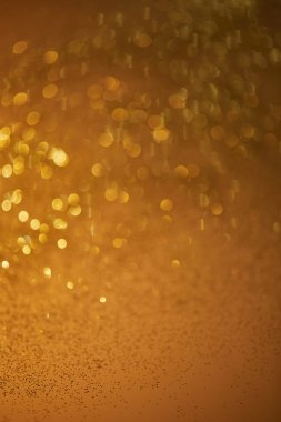 Golden bokeh christmas background with falling glittering sequins stock vector