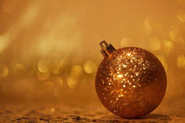 golden glittering christmas ball for decoration on tabletop with sequins
