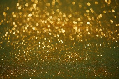 Golden and green bokeh christmas background with shiny glitter stock vector