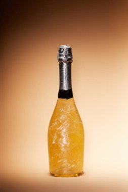 bottle of glittering champagne isolated on beige, christmas concept