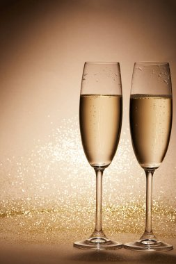 two glasses of champagne with glitter on tabletop, christmas concept
