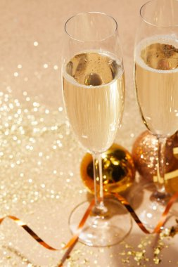 Close up of  two glasses of champagne and christmas toys with glitter on tabletop stock vector