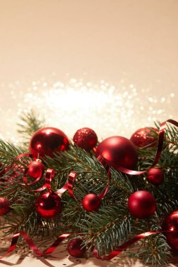 red shiny christmas balls and pine branch on glittering tabletop