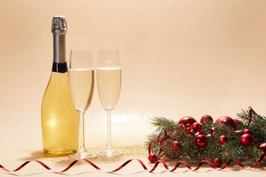 bottle and glasses of champagne, christmas balls and pine branch on glittering tabletop