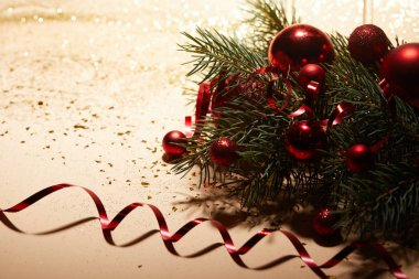 red shiny christmas toys, wavy ribbon and pine branch on glossing surface