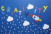 Fotografie Weiße Wolken und Rakete auf blauem Hintergrund mit Kreativität -Schriftzug