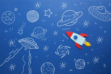 creative rocket on blue paper background with universe icons