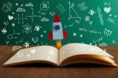 Fotografie open book with colorful rocket on wooden table with math icons