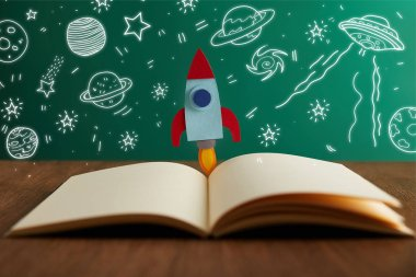 open book with colorful rocket on wooden table with universe icons